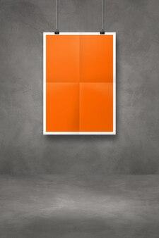 Cartaz dobrado laranja pendurado em uma parede de concreto escuro com clipes. modelo de maquete em branco
