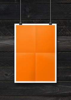Cartaz dobrado laranja pendurado em uma parede de madeira preta com clipes. modelo de maquete em branco