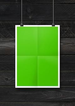 Cartaz dobrado verde pendurado em uma parede de madeira preta com clipes. modelo de maquete em branco