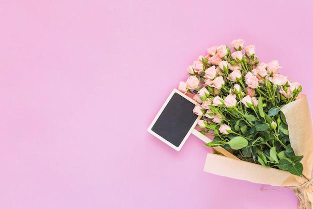 Cartaz em miniatura e rosas cor de rosa contra o pano de fundo rosa