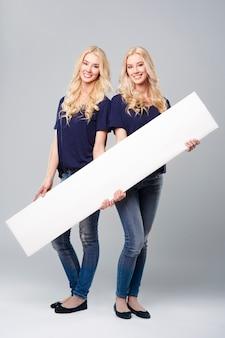 Cartaz horizontal segurado por meninas