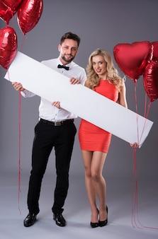 Cartaz horizontal segurado por um casal elegante