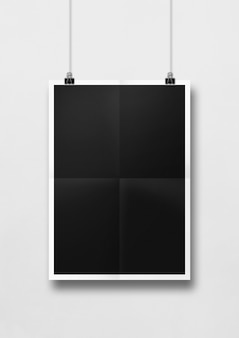 Cartaz preto dobrado pendurado em uma parede branca com clipes