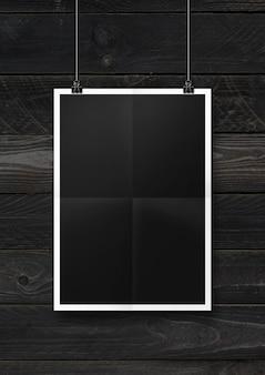 Cartaz preto dobrado pendurado em uma parede de madeira com clipes.