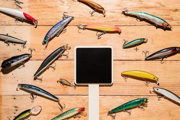 Cartaz preto em branco cercado com iscas de pesca coloridos na mesa de madeira