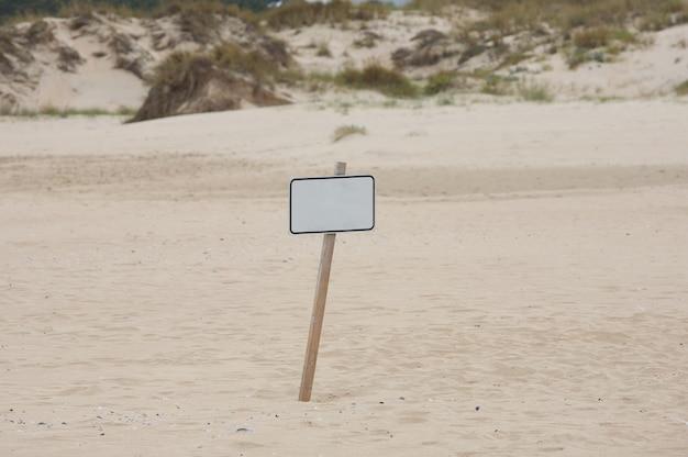 Cartaz solitário no meio da areia