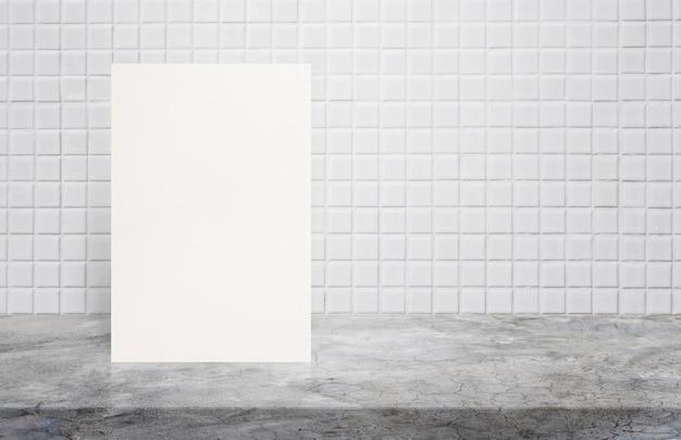 Cartaz vazio do livro branco no tampo da mesa de lustro do cimento na parede branca do azulejo do mosaico.