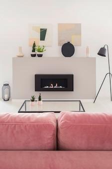 Cartazes acima da lareira no interior do apartamento branco com lâmpada preta e sofá rosa. foto real
