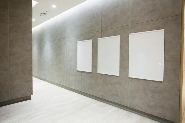 Cartazes quadrados em branco na parede de concreto no salão vazio