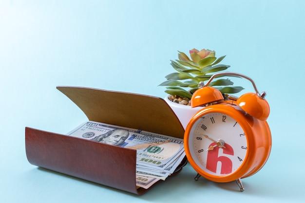 Carteira aberta marrom com dólares, despertador laranja e planta suculenta em uma superfície azul, closeup.