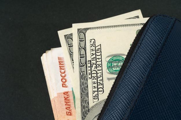 Carteira azul cheia de dinheiro, rublos russos e dólares americanos