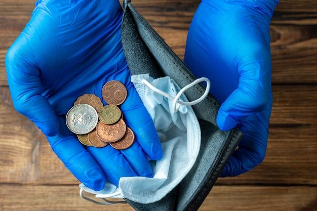 Carteira azul vazia com máscara protetora nas mãos após a crise econômica financeira