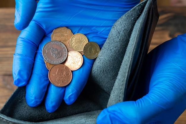 Carteira azul vazia nas mãos em luvas médicas segurando moedas após a crise econômica financeira