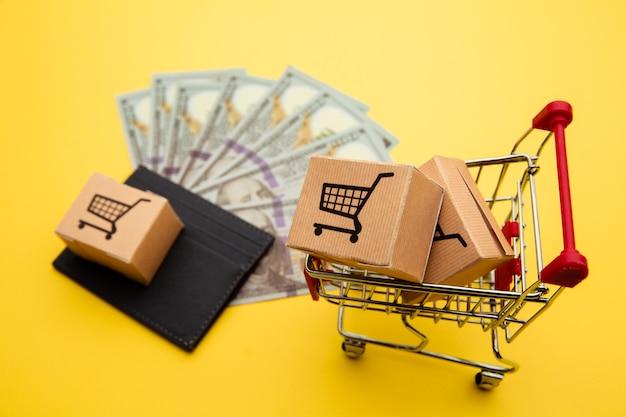Carteira cinza com notas de cem dólares, caixas de entrega e carrinho de compras em amarelo