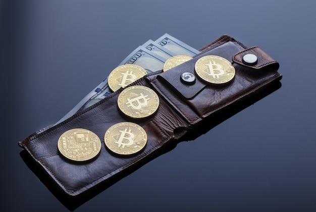 Carteira com bitcoins de ouro e notas de cem dólares