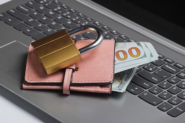 Carteira com dinheiro e bloqueio no teclado do laptop