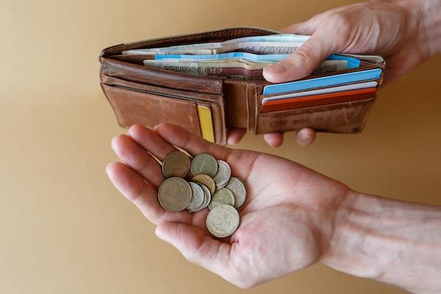 Carteira com dinheiro e moedas nas mãos do homem