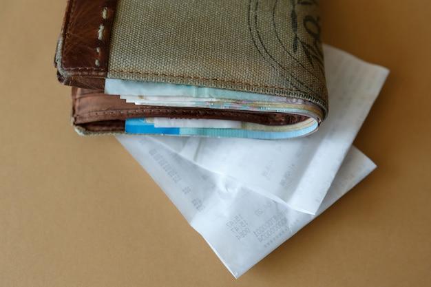 Carteira com dinheiro e um cheque administrativo da loja