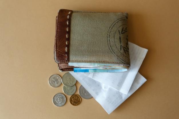 Carteira com dinheiro, moedas e um cheque administrativo da loja