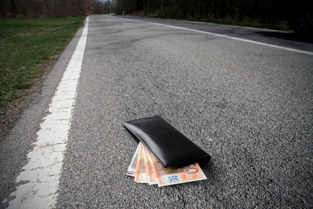 Carteira com dinheiro na estrada