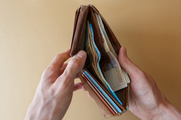 Carteira com dinheiro nas mãos do homem