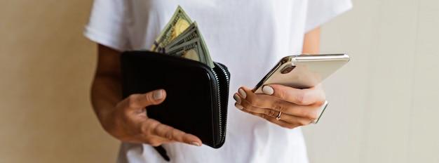 Carteira com dólares americanos e celular nas mãos da mulher