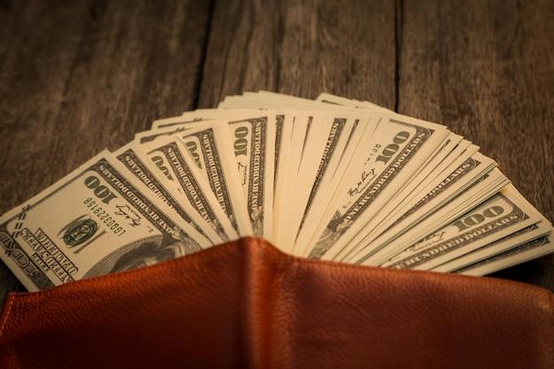 Carteira com dólares americanos na mesa de madeira