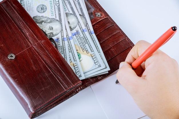Carteira com notas de cem dólares em um fundo cinza. uma caneta e uma folha em branco nas mãos da garota.