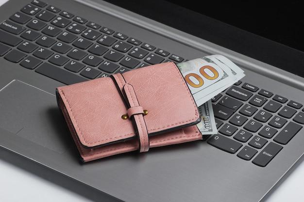 Carteira com notas de dólar no teclado do laptop