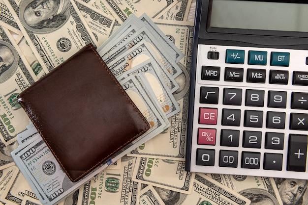 Carteira completa de notas de 100 dólares com calculadora como plano de fundo do negócio, conceito de economia