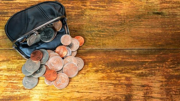 Carteira de bolso de couro preto aberta cheia de várias moedas. crise financeira, pobreza, falta de dinheiro.
