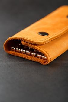 Carteira de capa marrom para chaves feita de couro genuíno nobuck no escuro. rebites feitos à mão e costura closeup