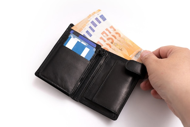 Carteira de cavalheiro com cartões de crédito com uma das mãos tirando notas em fundo branco