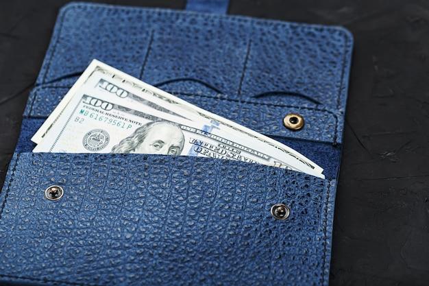 Carteira de couro azul com notas de cem dólares