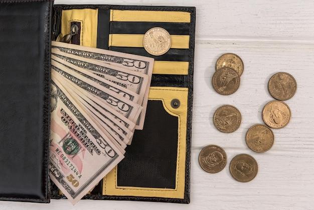 Carteira de couro com dólares americanos e centavos na mesa de madeira branca, conceito de finanças