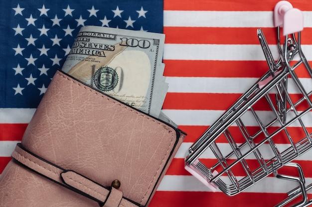 Carteira de couro com notas de cem dólares e carrinho de compras na bandeira dos eua
