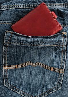 Carteira de couro marrom no bolso de trás da calça jeans azul