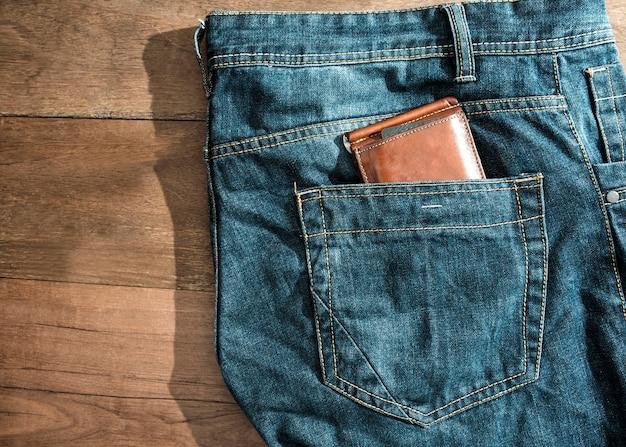 Carteira de couro marrom no bolso de trás jeans azul.