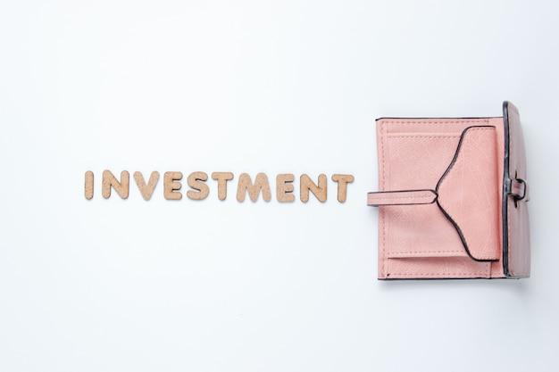 Carteira de couro na moda na superfície branca com investimento de texto.