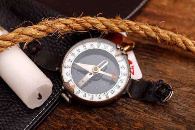 Carteira de couro preta com velho baralho e corda com bússola