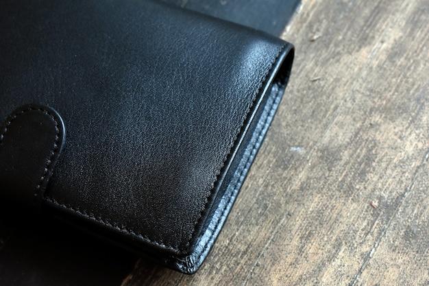 Carteira de couro preto sobre fundo claro de madeira