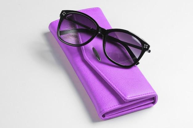 Carteira de couro roxa, close dos óculos de sol no fundo branco