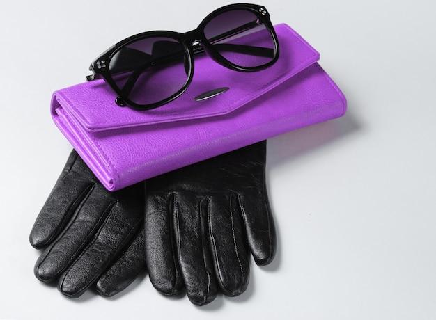Carteira de couro roxo, óculos de sol, close-up de luvas em fundo branco