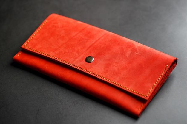 Carteira de couro vermelha em uma opinião superior do fundo escuro. close-up, detalhes da bolsa, rebite e firmware