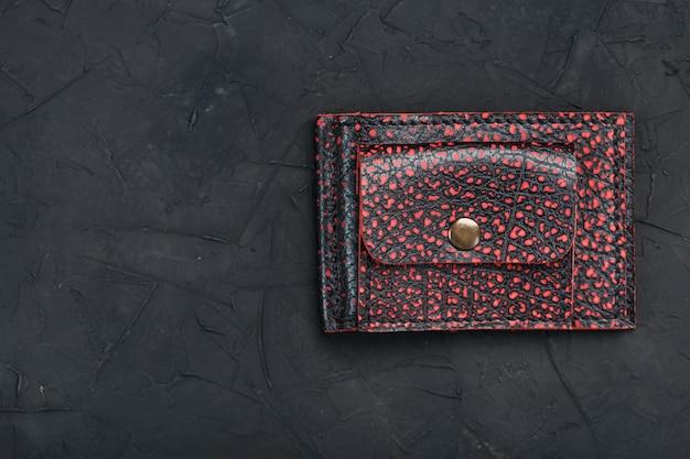 Carteira de couro vermelho e preto sobre uma mesa preta.