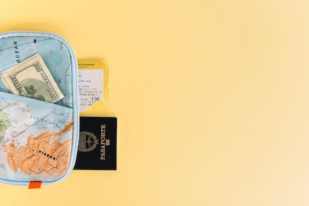 Carteira de mapa com moeda; passaporte e bilhete em fundo amarelo