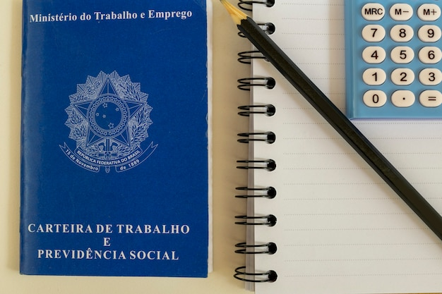 Carteira de trabalho brasileira, caderno espiral, lápis e calculadora.