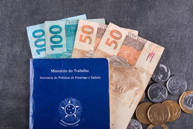 Carteira de trabalho brasileira com notas e moedas reais.