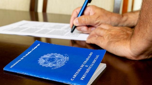 Carteira de trabalho brasileira e em segundo plano assinando contrato de trabalho