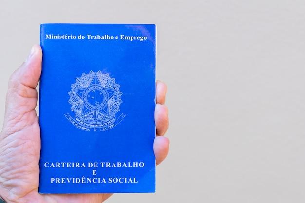 Carteira de trabalho brasileira. mão segurando a placa de trabalho com espaço para texto.